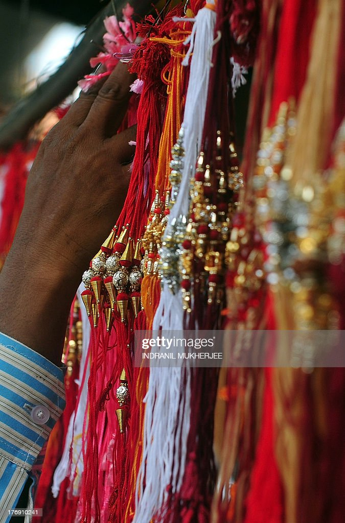 An Indian Muslim shopkeeper hangs 'rakhis' (sacred thread) for display at a market ahead of the Hindu festival of Raksha Bandhan in Mumbai on August 19, 2013. The annual Hindu festival of Raksha Bandhan, which commemorates the abiding ties between siblings of opposite sex, is marked by a very simple ceremony in which a woman ties a rakhi, which may be a colorful thread, a simple bracelet, or a decorative string, around the wrist of her brother. This year's Raksha Bandhan will be celebrated across India on August 20. AFP PHOTO/Indranil MUKHERJEE