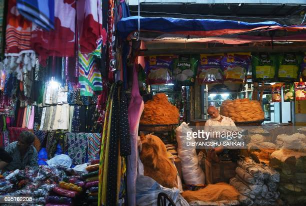An Indian Muslim vendor takes a nap as he waits for customers in his temporary shop for vermicelli snacks next to a garment vendor's store during the...