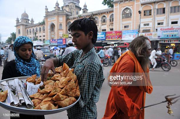 An Indian Muslim woman buys samosa snacks prior to iftar the breaking of the fast as a Hindu priest walk past on the first day of the holy month of...