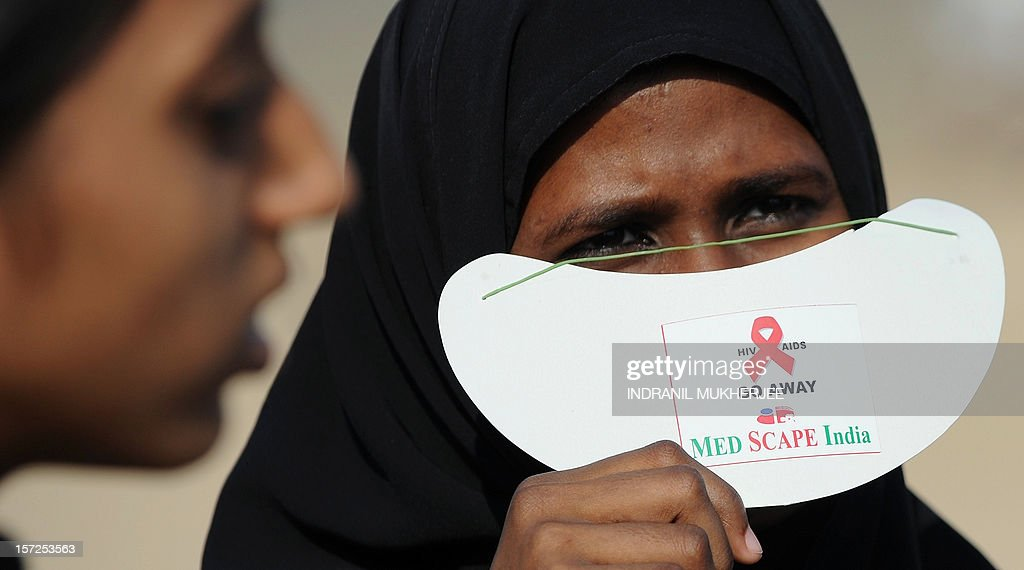 An Indian Muslim woman covers her face with a sun-visor as attends a rally on World AIDS Day in Mumbai on December 1, 2012. The UNAIDS agency says some 2.5 million Indians are living with HIV, many of them ostracised by their communities . AFP PHOTO/INDRANIL MUKHERJEE
