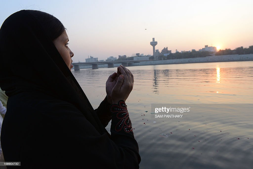 An Indian Muslim woman prays as she faces westward while observing 'Muhorram Ka Chalisa', which marks forty days after Moharram, on the banks of the Sabarmati river in Ahmedabad on January 3, 2013. Thousands of Muslims thronged the Sabarmati river bank near Khanpur Gate in Ahmedabad to mark the occasion. AFP PHOTO / Sam PANTHAKY