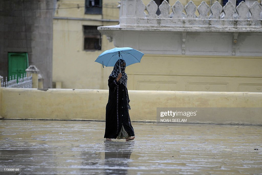 An Indian Muslim woman walks with an umbrella in the monsoon rains on the first friday of the holy month of Ramadan at Mecca Masjid in Hyderabad on July 12, 2013. Islam's holy month of Ramadan is calculated on the sighting of the new moon and Muslims all over the world are supposed to fast from dawn to dusk during the month. AFP PHOTO / Noah SEELAM