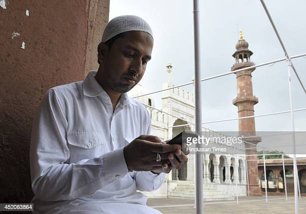 An Indian Muslim youth reading verses of Holy Quran on a smart phone during the holy month of Ramadan at Moti Masjid on July 12 2014 in Bhopal India...