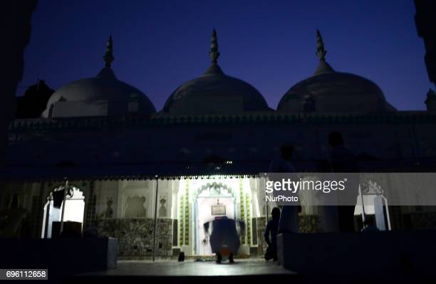 An Indian musllim devotee offers prayers after breakinng his fast as others walk on during holy fasting month of Ramadan at an old mosque on the...