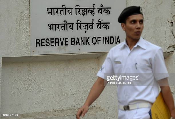 An Indian naval officer walks past the Reserve Bank of India headquarters in Mumbai on October 29 2013 India's new central bank governor has hiked...