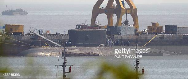 An Indian Navy submarine believed to be the Russianbuilt INS Sindhuratna is seen anchored at the naval dockyard as a fire truck and support crew are...