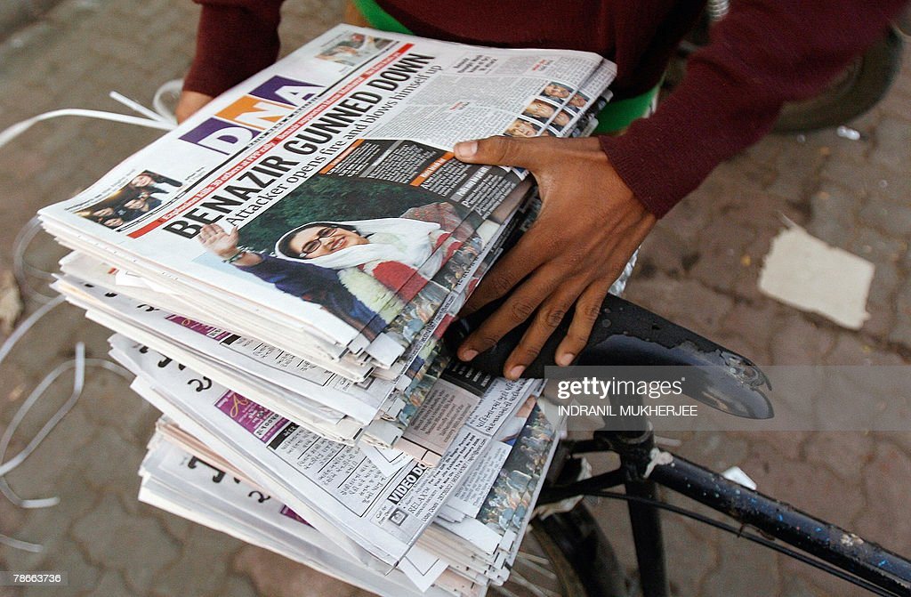An Indian newspaper delivery places newspapers on his bike in Mumbai early 28 December 2007, with the reports of the assassination of former Pakistani premier Benazir Bhutto. Bhutto was assassinated by a suicide bomber, plunging the nation into one of the worst crises in its history and raising alarm around the world. Violence erupted in cities across Pakistan as mobs went on the rampage in a wave of anger that left at least 10 people dead and dozens wounded, officials said. AFP PHOTO/Indranil MUKHERJEE