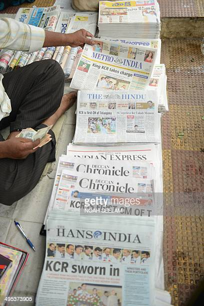 An Indian newspaper distributor sorts papers reporting on the newlyformed Telangana state's first Chief Minister K Chandra Sekhar Rao taking office...