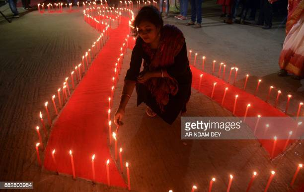 TOPSHOT An Indian NGO volunteer lights candles placed on the ground in the shape of a red ribbon during an awareness rally on the eve of World Aids...