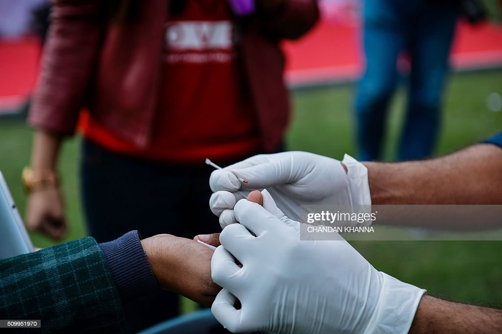 An Indian nurse carries out tests for HIV/AIDS during an event to promote the prevention of sexually transmitted diseases (STDs), and unwanted preganancies, through condom distribution and to create awareness towards safe sex in New Delhi on February 13, 2016. AFP PHOTO / Chandan KHANNA / AFP / Chandan Khanna