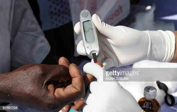 An Indian nurse collects a blood sample from a patient using a glucometer at a free Diabetic health check up camp in Hyderabad on November 1 2009...