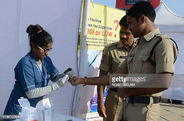 An Indian nurse collects a blood sample from police using a glucometer at a free diabetic health check up camp on World Health Day in Hyderabad on...
