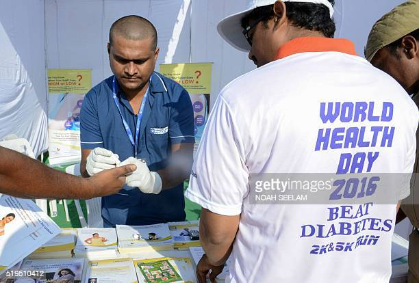 An Indian nurse collects a blood sample using a glucometer at a free diabetic health check up camp on World Health Day in Hyderabad on April 7 2016...