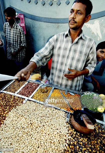 An Indian nut vendor sells assorted nuts at his stand on a sidewalk in the streets of Bombay 11 December 2003 as his son looks on Bombay street food...