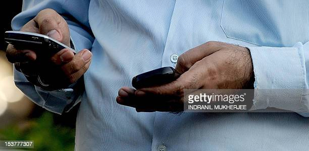 An Indian officegoer checks a text message on his mobile phone in Mumbai on September 27 2011 India's telecom watchdog the Telecom Regulatory...