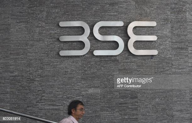An Indian officegoer walks past the Bombay Stock Exchange logo at the BSE building in Mumbai on July 25 2017 India's stock markets hit record highs...