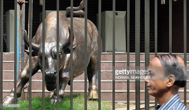 An Indian officegoer walks past the statue of the bronze Bull outside the Bombay Stock Exchange in Mumbai on August 8 2011 India's central bank said...