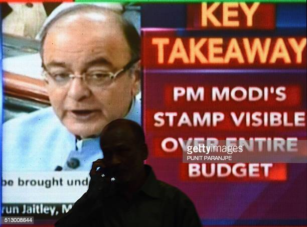 An Indian officeworker walks past a digital screen showing Finance Minister Arun Jaitley delivering the budget speech at Parliament at the Bombay...