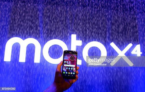 An Indian official holds the newly launched Lenovoowned Motorola Moto X4 smartphone during a promotional event in New Delhi on November 13 2017 / AFP...