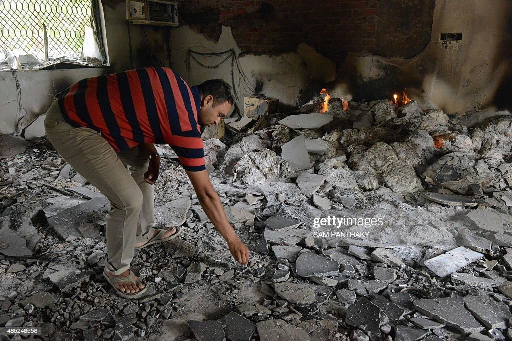 An Indian official looks through the damaged remains of a record storage room destroyed by rioters at the Ahmedabad Municipal Corporation office in...
