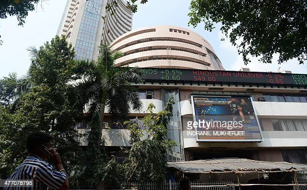 An Indian onlooker watches the digital broadcast on the facade of the Bombay Stock Exchange during intraday trade in Mumbai on March 7 2014 Indian...