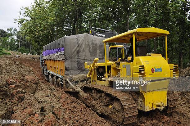 An Indian operator attempts to use a bulldozer to move a truck from heavy mud on National Highway 44 at Khasiapunji some 205 kms north of Agartala on...