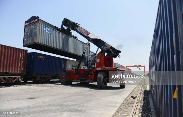 An Indian operator controls a mobile crane as it unloads containers from a railway rack at the Inland Container Depot at Sachana village some 50 kms...