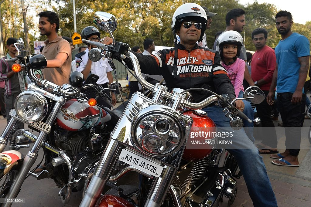 an indian owner of a harley davidson motorcycle poses as he takes