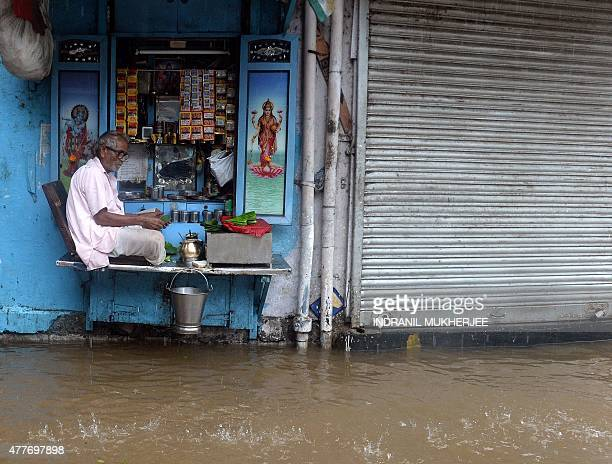 An Indian paanbeetle leaf seller waits for customers at his shop on a waterlogged street in Mumbai on June 19 2015 Heavy monsoon showers lashed...