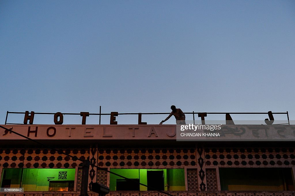 An Indian painter paints the rooftop sign of a hotel in the old quarters of New Delhi on May 5, 2016. / AFP / CHANDAN