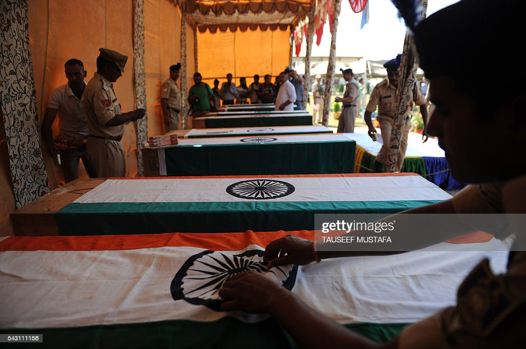 An Indian paramilitary personnel adjusts the national flag covering the coffin of a colleague killed in an ambush during a ceremony in Srinagar on June 26, 2016. At least eight Indian paramilitary soldiers and two suspected rebels were killed June 25 near Srinagar in India-administered Kashmir when a group of armed militants ambushed the soldiers' convoy, police said. Four militants sprayed bullets on the convoy carrying members of India's Central Reserve Police Force (CRPF) near Pampore town, killing five soldiers instantly and wounding 20, inspector general of police for the region, Javaid Gillani, told AFP. / AFP / TAUSEEF