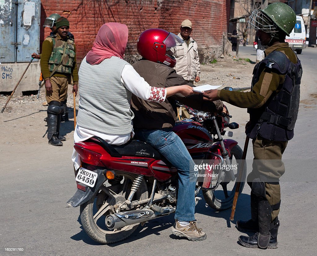 An Indian paramilitary soldier checks the papers of Kashmiri Muslims before allowing them to move forward during a curfew-like restriction on March 7, 2013 in Srinagar, the summer capital of Indian Administered Kashmir, India. Clashes erupted in most parts of Kashmir today leaving scores of people injured. Meanwhile Indian authorities imposed curfew-like restrictions for the second consecutive day in most parts of Kashmir following the killing of a Kashmiri youth by the Indian army in North Kashmir's Baramulla district.