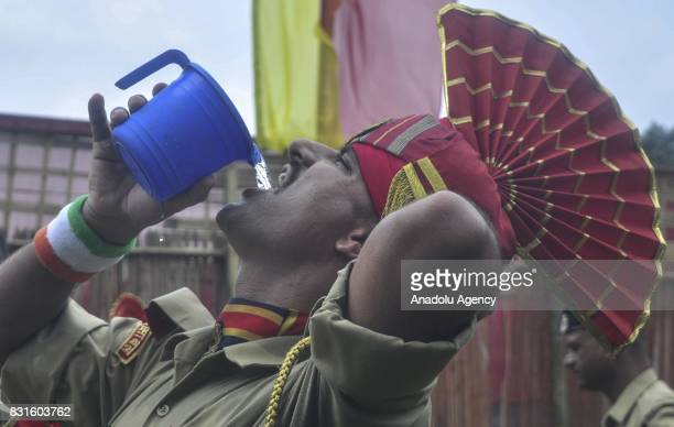 An Indian paramilitary soldier drinks water after the march during the Independence Day celebrations in Agartala India on August 15 2017
