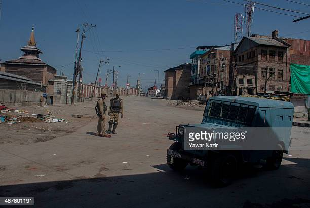 An Indian paramilitary soldier guards a deserted road in the old city during a curfew following a killing of a youth on May 01 2014 in Srinagar the...