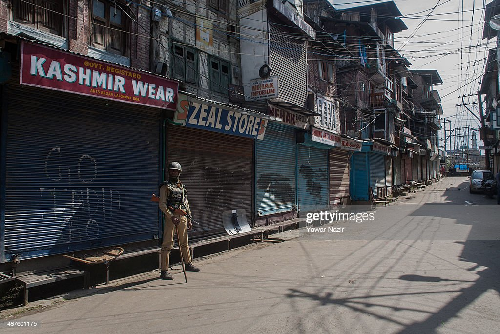 An Indian paramilitary soldier guards the deserted roads in the main city during a curfew following a killing of a youth on May 01, 2014 in Srinagar, the summer capital of Indian-administered Kashmir, India. Kashmir remained on boil a day after a youth was shot dead by Indian armed government forces in the Old City of Srinagar. Two persons including a woman were also wounded when Indian forces fired at Kashmiri stone hurling protesters who were shouting 'down with India' slogans. The Indian forces in Kashmir clamped a stringent curfew in the region to stop anti-India protests from escalating while as a shutdown was observed to protest the killing of the youth.