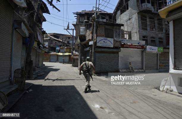 TOPSHOT An Indian paramilitary soldier patrols during a curfew in downtown Srinagar on May 30 2017 Authorities imposed a curfew in many parts of the...
