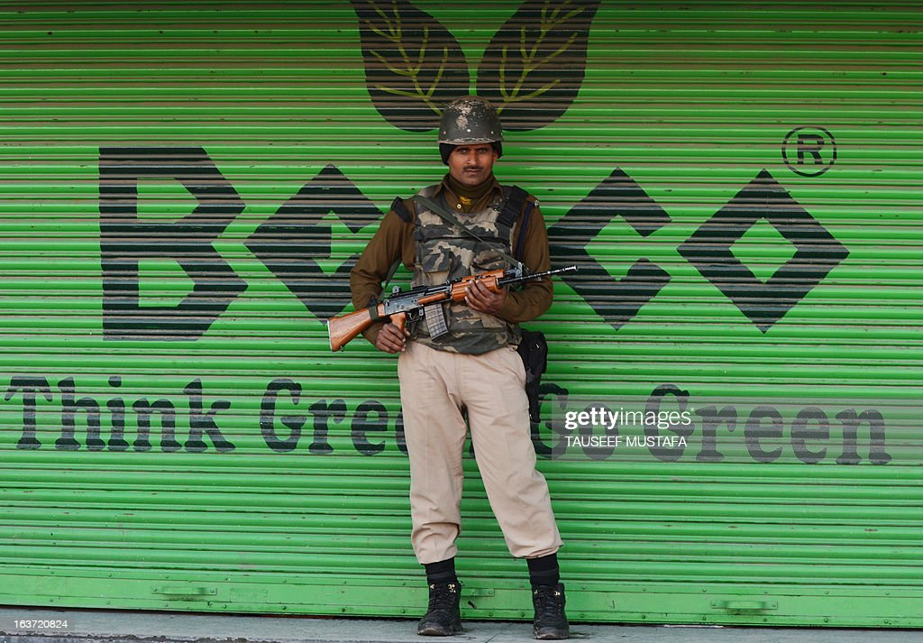 An Indian Paramilitary soldier stand guard during the second day of curfew, imposed on the Kashmiri summer capital in Srinagar on March 15, 2013. Indian-administered Kashmir's main city was under curfew after the killing of five paramilitary police and the death of two civilians cranked up tensions in the disputed region. Kashmir's inspector general of police Abdul Gani Mir said a round-the-clock curfew order had been imposed in the city of Srinagar while there were similar restrictions in other towns and villages in the Kashmir Valley. AFP PHOTO/ Tauseef MUSTAFA