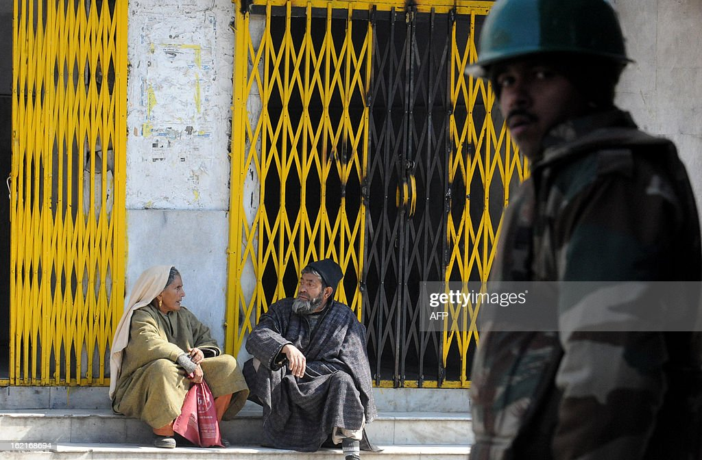 An Indian paramilitary soldier stands guard as Kashmiri couple sit during a shutdown in Srinagar on February 20, 2013. A separatist alliance, All Parties Hurriayt Conference, opposed to Indian rule in Kashmir called for a two-day strike in to press the demanded for return of Afzal Guru's mortal remains to his family. Guru was executed on February 9, 2013 and buried inside a high security prison in New Delhi after he was convicted of his role in a deadly attack on Indian parliament in 2001. AFP PHOTO/ Rouf BHAT