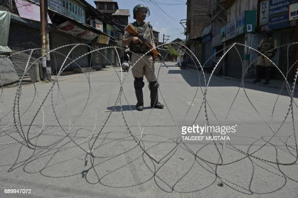 TOPSHOT An Indian paramilitary soldier stands guard during a curfew in downtown Srinagar on May 30 2017 Authorities imposed a curfew in many parts of...