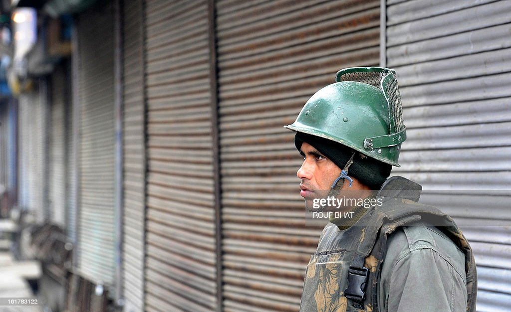 An Indian paramilitary soldier stands guard during a strike in Srinagar on February 16, 2013. A curfew imposed in Indian Kashmir after the execution of a separatist convicted over a 2001 attack on parliament was lifted Saturday but a strike against the hanging paralysed the region. AFP PHOTO/ Rouf BHAT
