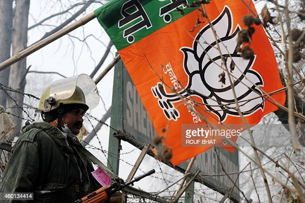 An Indian paramilitary soldier stands guard next to a Bharatiya Janata Party campaign flag during a curfew in Srinagar on December 8 2014 Prime...