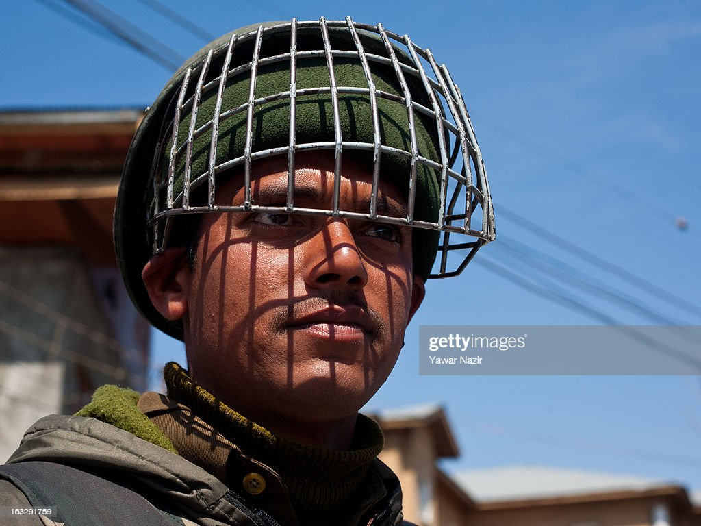 An Indian paramilitary soldier stands guard on a road during a curfew-like restriction on March 7, 2013 in Srinagar, the summer capital of Indian Administered Kashmir, India. Clashes erupted in most parts of Kashmir today leaving scores of people injured. Meanwhile Indian authorities imposed curfew-like restrictions for the second consecutive day in most parts of Kashmir following the killing of a Kashmiri youth by the Indian army in North Kashmir's Baramulla district.