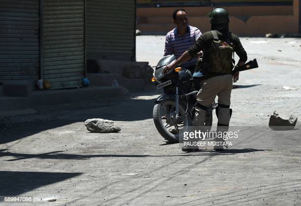 An Indian paramilitary soldier stops a motorcyclist during a curfew in downtown Srinagar on May 30 2017 Authorities imposed a curfew in many parts of...