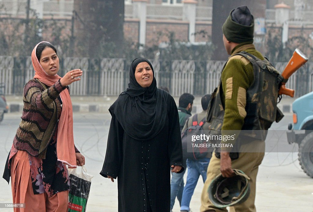 An Indian paramilitary soldier stops Kashmiri woman in an empty street during a restrictions for a Muharram procession in Srinagar on November 23, 2012. Authorities imposed restrictions in parts of Srinagar, the summer capital of Kashmir, to thwart planned Muharram processions as police detained more than a dozen protesters and fired teargas to disperse participants. AFP PHOTO/ Tauseef MUSTAFA