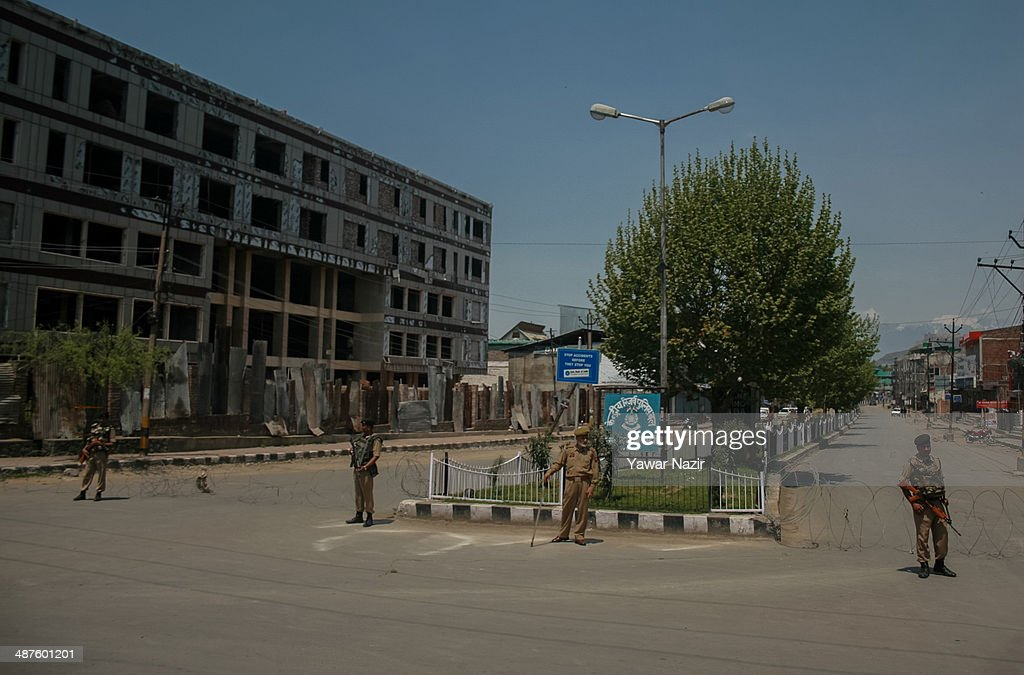 An Indian paramilitary soldiers guard the deserted roads in the Old City during a curfew following a killing of a youth on May 01, 2014 in Srinagar, the summer capital of Indian-administered Kashmir, India. Kashmir remained on boil a day after a youth was shot dead by Indian armed government forces in the Old City of Srinagar. Two persons including a woman were also wounded when Indian forces fired at Kashmiri stone hurling protesters who were shouting 'down with India' slogans. The Indian forces in Kashmir clamped a stringent curfew in the region to stop anti-India protests from escalating while as a shutdown was observed to protest the killing of the youth.