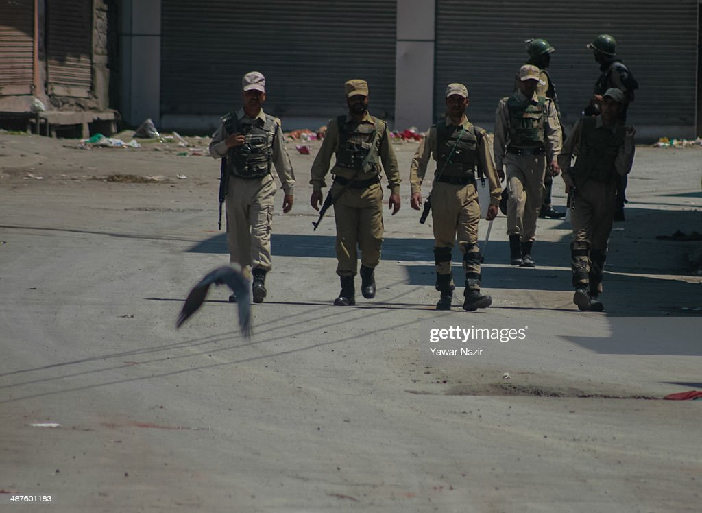 An Indian paramilitary soldiers patrol the deserted roads in the Old City during a curfew following a killing of a youth on May 01, 2014 in Srinagar, the summer capital of Indian-administered Kashmir, India. Kashmir remained on boil a day after a youth was shot dead by Indian armed government forces in the Old City of Srinagar. Two persons including a woman were also wounded when Indian forces fired at Kashmiri stone hurling protesters who were shouting 'down with India' slogans. The Indian forces in Kashmir clamped a stringent curfew in the region to stop anti-India protests from escalating while as a shutdown was observed to protest the killing of the youth.