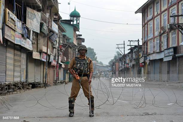 TOPSHOT An Indian paramilitary troop stands guard during a curfew in Srinagar on July 10 2016 Eight protesters were killed and more than 200 others...