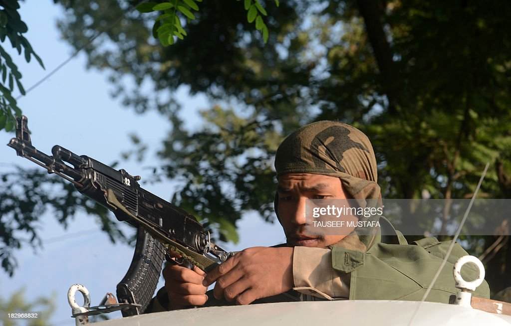 An Indian paramilitary trooper adjusts his weapon while travelling on the top of a vehicle on the outskirts of Srinagar on October 3, 2013, following an encounter with suspected militants in the restive state. Four policemen were injured in a late-night encounter on the outskirts of Srinagar, as suspected militants who were hiding inside a house escaped under the cover of darkness police officials said. AFP PHOTO/Tauseef MUSTAFA