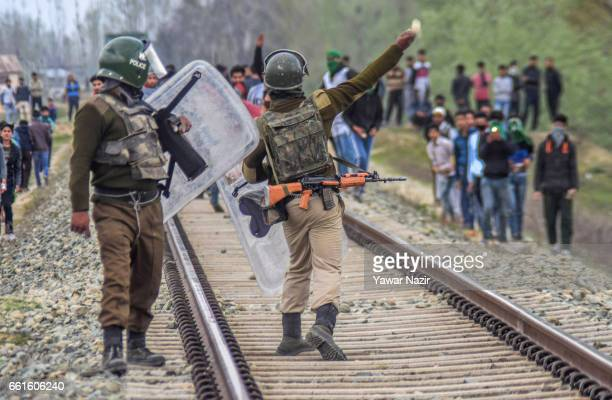 An Indian paramilitary trooper gestures after throwing stones at Kashmiri Muslim protesters during an anti India protest against the recent civilian...