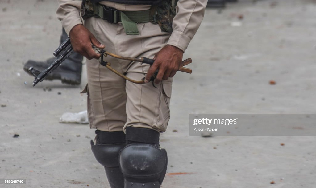 An Indian paramilitary trooper holds a catapult shoot stones at Kashmiri Muslim protester during an anti India protest on May 19, 2017 in Srinagar, the summer capital of Indian administered Kashmir, India. Indian government forces used teargas shells to disperse dozens of Kashmiri Muslim protesters who were throwing stones at them during an anti Indian protest in the Old City of Srinagar, after Friday prayers.